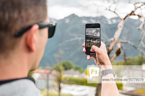 Male tourist taking smartphone photograph of mountain village  over shoulder view  Francenigo  Veneto  Italy