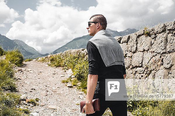 Geschäftsmann mit persönlichem Organisator  der einen Bergpfad hochwandert  Francenigo  Venetien  Italien