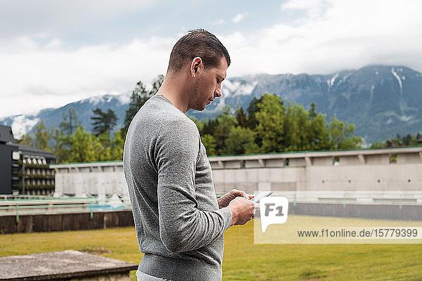 Mann schaut auf Smartphone in Bergdorf  Dolenci  Slowenien