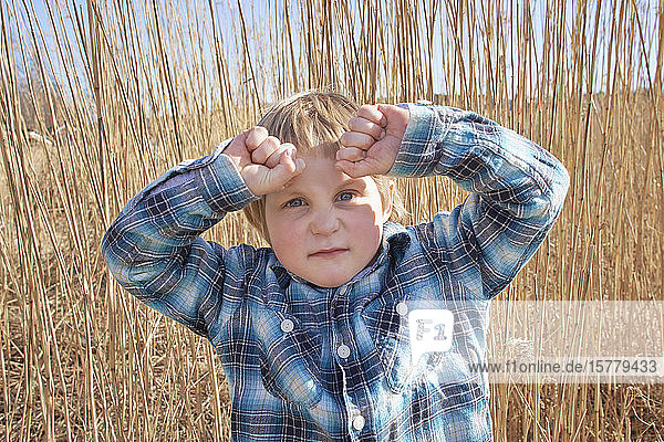 Boy with hands raised in reeds  portrait