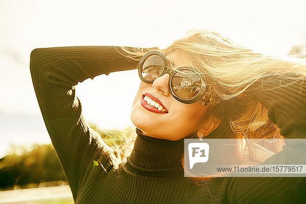 Porträt einer blonden Frau mit Sonnenbrille und lächelnden Händen im Haar