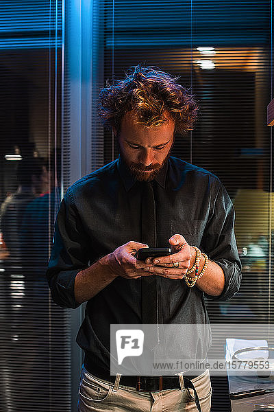 Mann schreibt auf der Party SMS mit Mobiltelefon