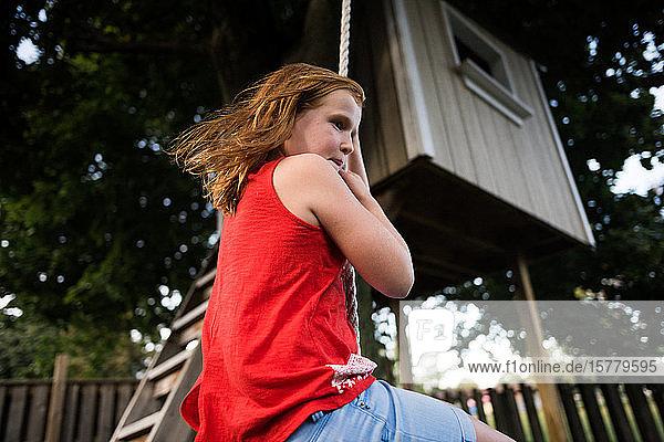Mädchen schwingt am Seil unter einem Baumhaus