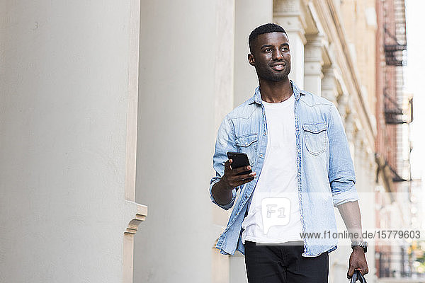 Young man with hand luggage holding cellphone in streets of New York  US