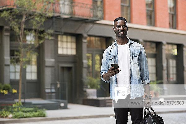 Junger Mann mit Handgepäck mit Handy in den Straßen von New York  USA