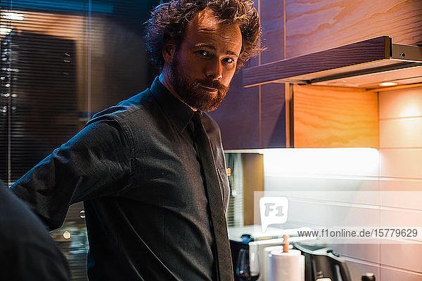 In der Küche stehender Mann