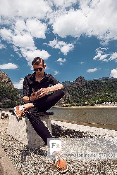 Mann mit Mobiltelefon am Strand  Draja  Vaslui  Rumänien