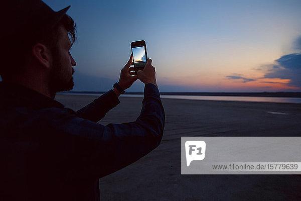 Mann mit Hut beim Fotografieren eines Sonnenuntergangs am Strand  Odessa  Ukraine