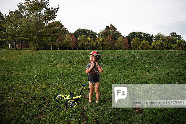 Junge befestigt Helm im Park