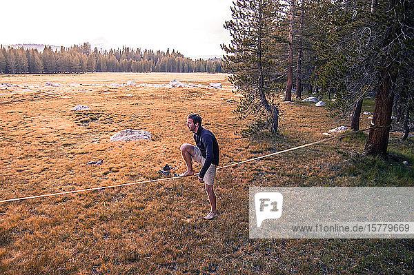 Junger Mann beim Üben auf der Slackline  Tuolumne Meadows  oberer Teil des Yosemite Nationalparks  Kalifornien  USA