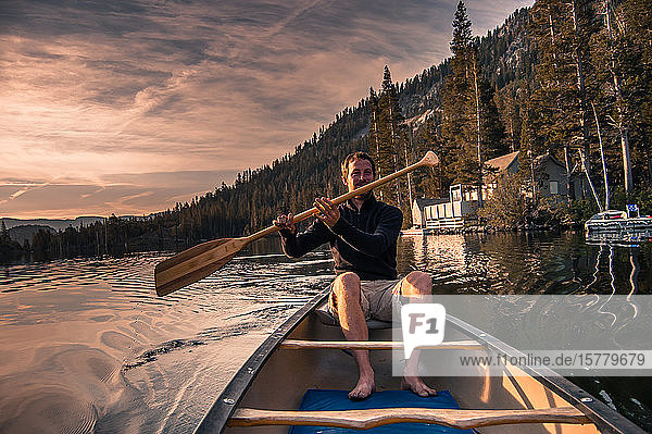 Young man canoeing on Echo Lake  High Sierras  California  USA