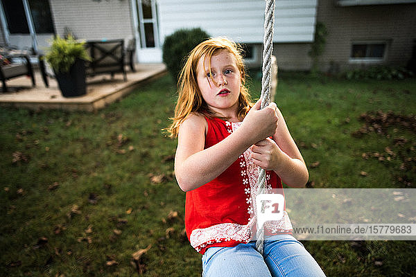 Mädchen schwingt am Seil im Garten