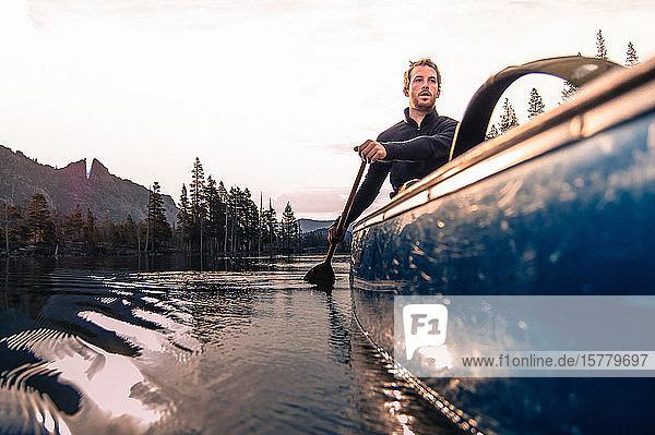 Junger Mann beim Kanufahren auf dem Echo Lake  High Sierras  Kalifornien  USA