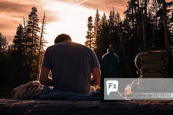 Junger männlicher Wanderer  der bei Sonnenuntergang eine Pause macht  Tuolumne Meadows  oberer Teil des Yosemite Nationalparks  Kalifornien  USA