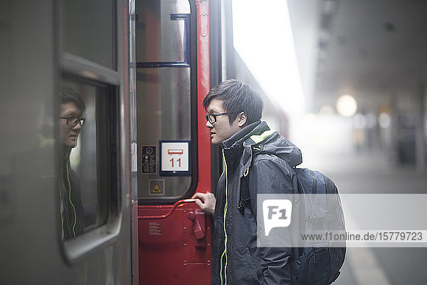 Young Asian man wearing glasses on railway platform  entering passenger train.