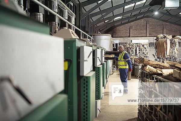 Arbeiter füllen Öfen mit Holz  um Holz in einer Holzrecyclinganlage zu trocknen.