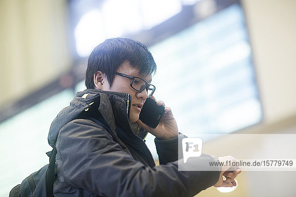 Young Asian man wearing glasses standing in railway station foyer  checking his watch and using mobile phone.