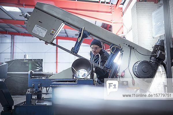 Ingenieur beim Sägen von Rohren in einer Metallverarbeitungsfabrik.