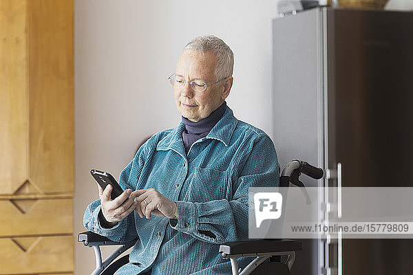 Senior woman sitting in a wheelchair  using mobile phone.