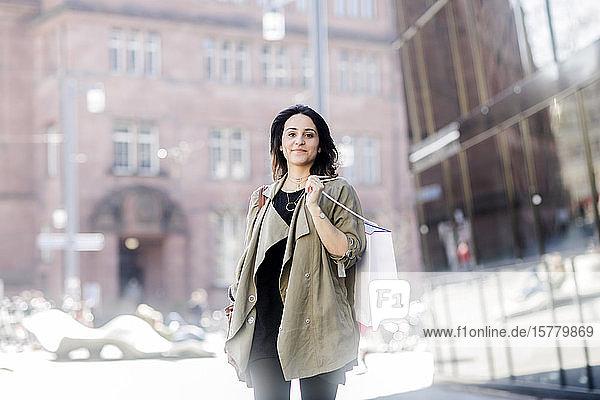 Porträt einer jungen Frau mit langen braunen Haaren  die einen beigen Mantel trägt  eine Einkaufstasche trägt und in die Kamera schaut.