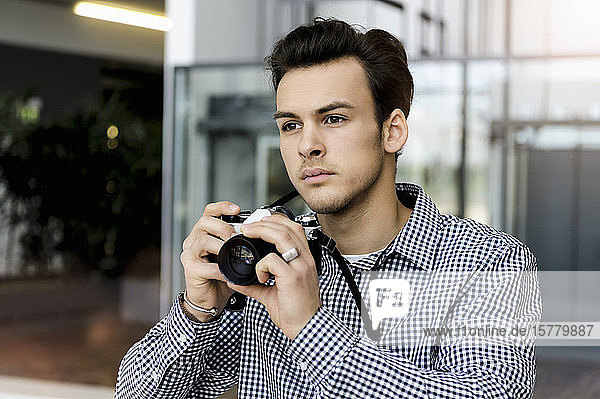 Portrait of young man with dark brown hair holding SLR camera.