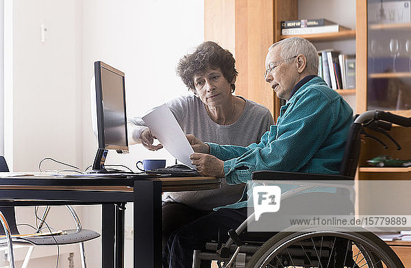 Senior woman sitting in a wheelchair at a computer  helper assisting with paperwork.