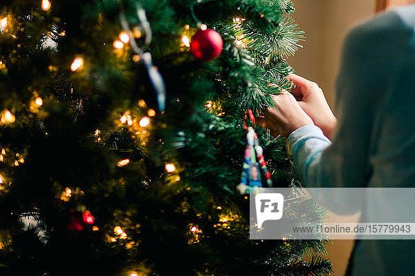 Person  die zu Hause den Weihnachtsbaum schmückt
