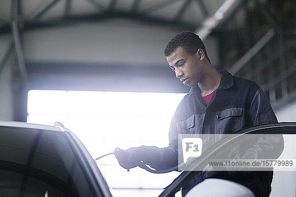 Handwerker repariert Windschutzscheibe eines Autos in der Werkstatt