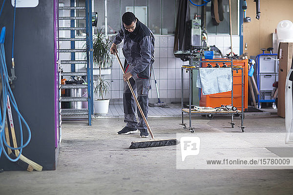 Workman cleaning floor in workshop