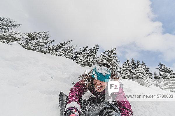 Frau  die in einem kanadischen Wald einen schneebedeckten Hang hinunterrutscht.