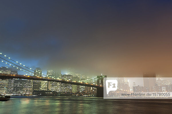 Manhattan skyline and Brooklyn bridge in mist at dusk  New York City  USA