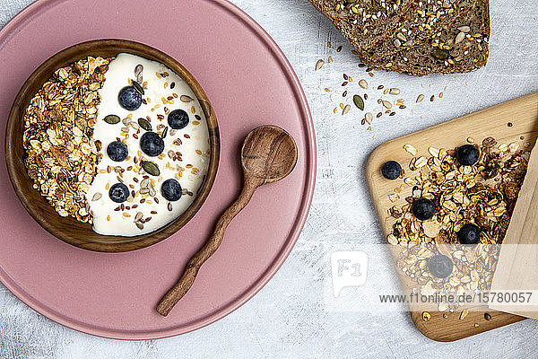 Bowl of muesli and blueberries on yogurt  multi-seed bread