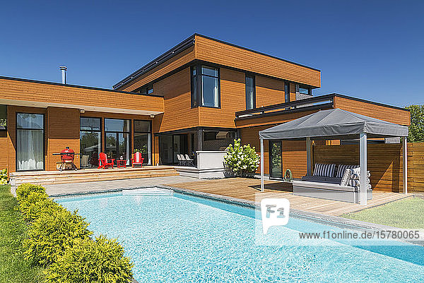 Exterior view of modern cube style home with stained horizontal wood cladding  swimming pool and wooden deck with gazebo canopy  Quebec  Canada.
