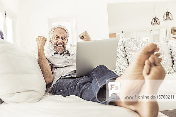 Mature man with laptop cheering on couch at home