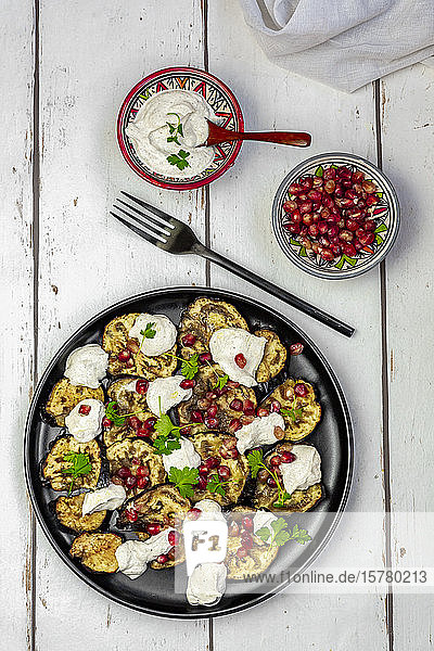 Baked eggplant slices with tahini  pomegranate seeds and parsley