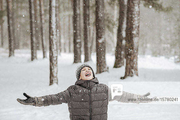 Portrait of boy catching snowflakes in winter forest
