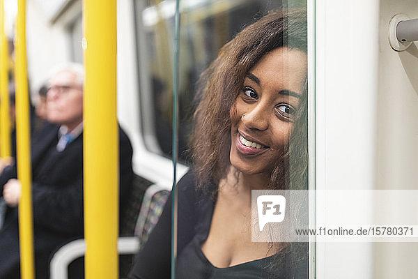 Porträt einer lächelnden jungen Frau in der U-Bahn