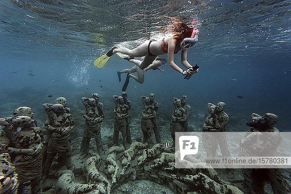 Frauen schwimmen in der Nähe von Unterwasser-Skulpturen von Jason deCaires Taylor  Insel Gili Meno  Bali  Indonesien