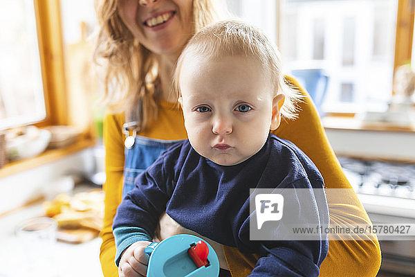 Porträt eines kleinen Jungen  der von seiner Mutter mit komischem Gesicht gehalten wird