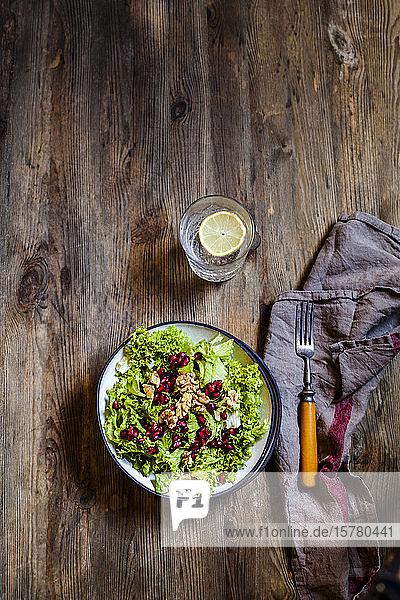 Schale mit grünem Salat mit Walnüssen und Granatapfelkernen