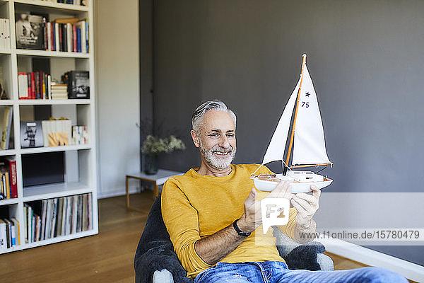 Smiling mature man at home holding model sailboat