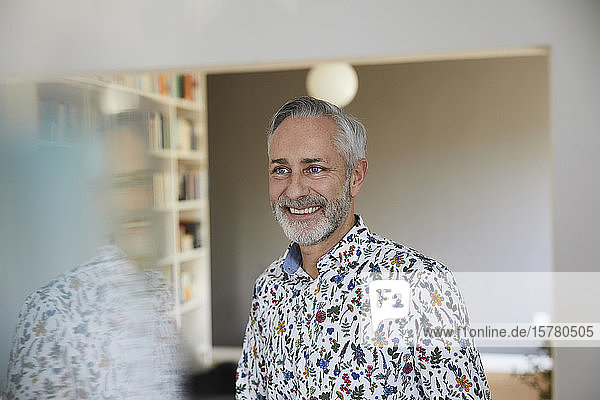 Portrait of smiling mature man wearing patterned shirt at home