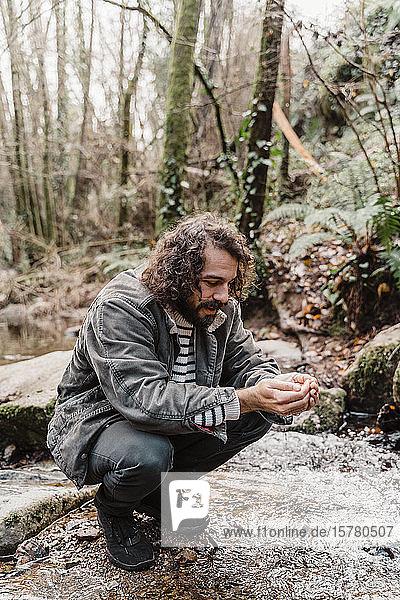 Junger Mann kauert am Bach im Wald und trinkt Wasser aus geschröpften Händen