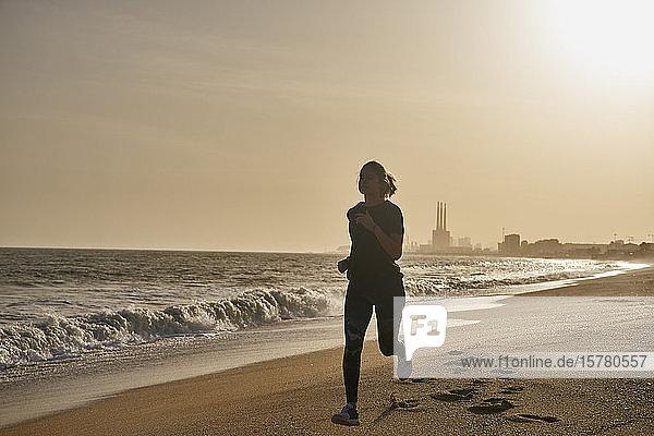 Junge Frau rennt bei Sonnenuntergang am Strand
