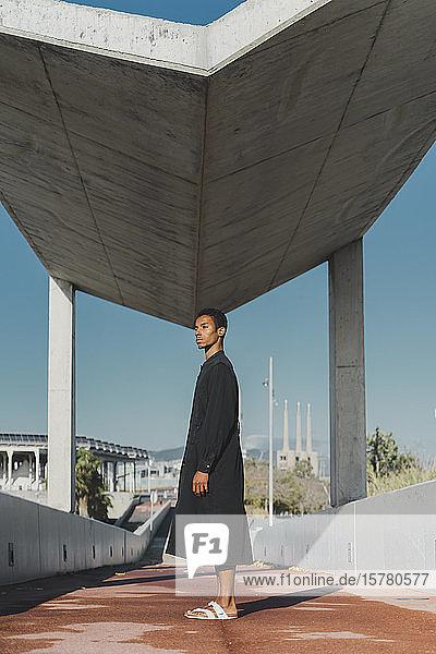 Junger Mann in schwarzem Kaftan auf einem Steg stehend