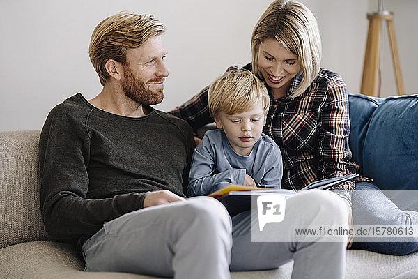 Familie schaut sich zu Hause Buch auf der Couch an