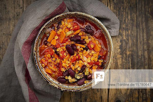 Schale mit veganem Chili mit roten Linsen  Selleriestangen  Kidneybohnen  Tomaten und Karotten