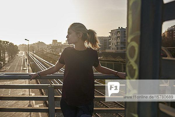 Sportliche junge Frau steht bei Sonnenuntergang auf einer Brücke