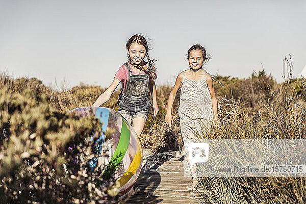 Zwei glückliche Mädchen rennen auf einer Strandpromenade in den Dünen Zwei glückliche Mädchen rennen auf einer Strandpromenade in den Dünen