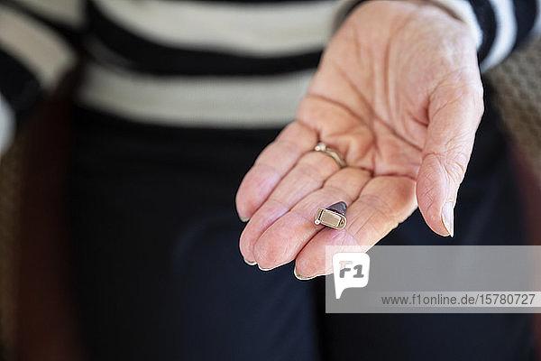 Hand einer älteren Frau mit modernem Hörgerät